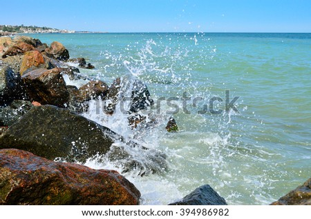 Waves splash on the large boulders on the beach - stock photo