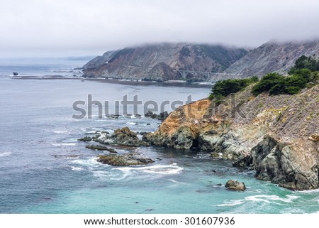 Waves splashing on huge rocks, off shore, along a rocky beach, close to the Big Sur Highway (California State Highway 1), on the California Central Coast, near Cambria CA. - stock photo