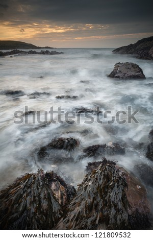 Waves swirl around the weed covered rocks in this small but exposed bay on the North Wales coastline. - stock photo