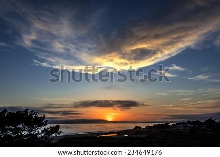 Waves, thunderheads, stormy, painted sky, and reflective sea at sunset, on Moonstone Beach, California Central Coast, near Cambria CA. - stock photo