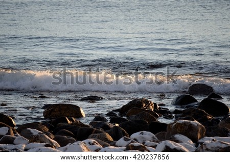 waves washing in over snow covered rocks on the sea shore - stock photo