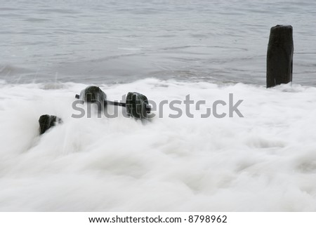 Waves washing over the groynes at Sandsend, Whitby, North Yorkshire, England, UK