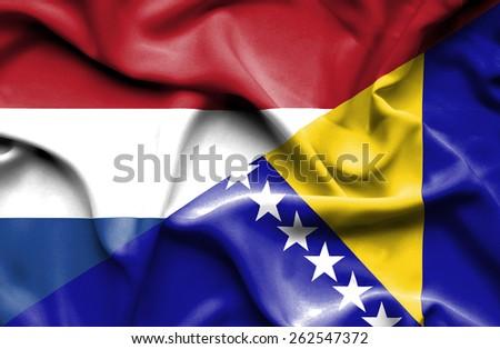 Waving flag of Bosnia and Herzegovina and Netherlands - stock photo