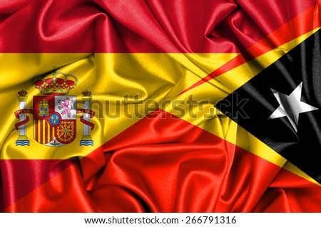 Waving flag of East Timor and Spain - stock photo