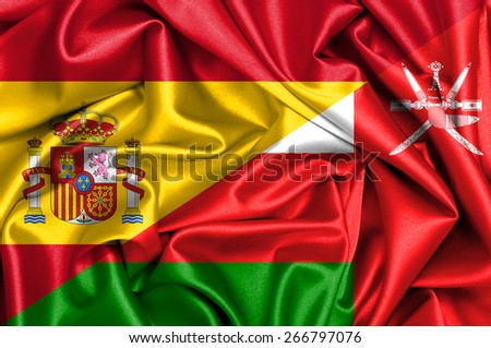 Waving flag of Oman and Spain - stock photo