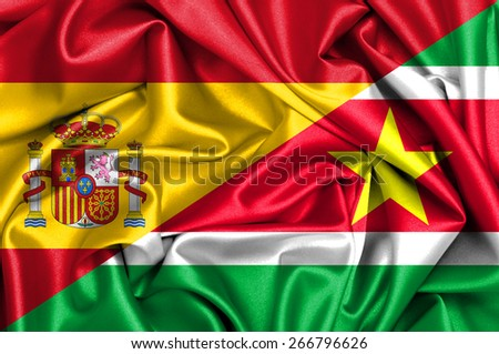 Waving flag of Suriname and Spain - stock photo