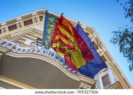 Waving flags of Valencia, Spain and European Union (EU) at the balcony of decorated administrative building, perspective view
