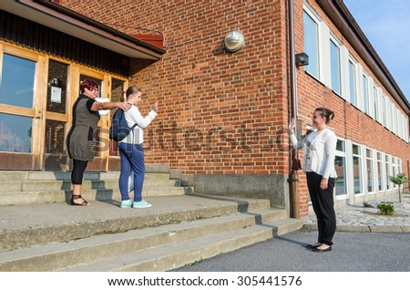 Waving goodbye in first school day  - stock photo