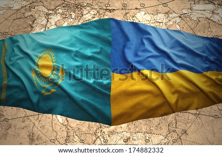 Waving Kazakh and Ukrainian flags of the political map of the world - stock photo