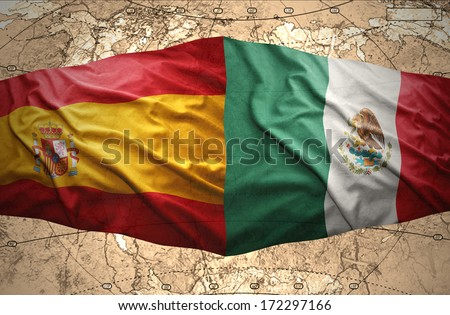 Waving Mexican and Spanish flags on the of the political map of the world