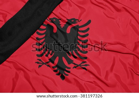 waving national flag of albania with black mourning ribbon  - stock photo