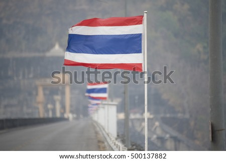 waving Thai flag of Thailand along the bridge for background, blur