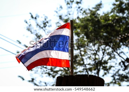 Waving Thai flag of Thailand on natural background.