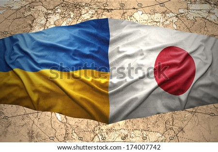Waving Ukrainian and Japanese flags of the political map of the world - stock photo