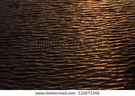 Waving, water surface with golden light on morning