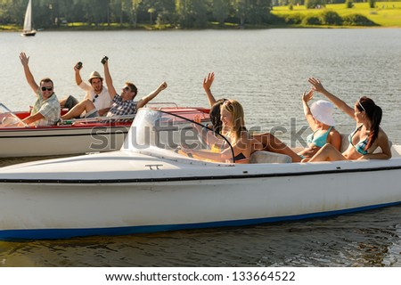 Waving young friends sitting in motorboats enjoying summertime - stock photo