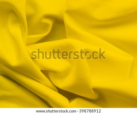 Wavy cloth or textile. Closeup of yellow texture.