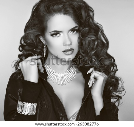 Wavy hair. Beautiful brunette girl model with long curled hairstyle, makeup and fashion jewelry. Black and white photo. - stock photo