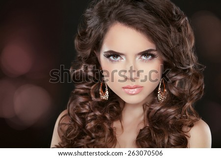 Wavy hair. Beautiful brunette girl model with long curly hairstyle, makeup and fashion jewelry. Black and white photo. - stock photo