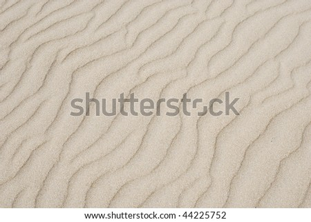 Wavy lines in sand.  Horizontally framed shot. - stock photo