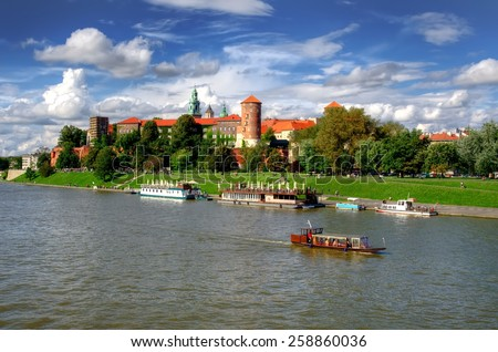 Wawel Royal Castle in Krakow. Tourist boats on Vistula river with Wawel Royal Castle in the background on sunny summer day, Poland. - stock photo