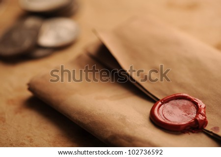 wax seal on a grunge paper, old coins on background