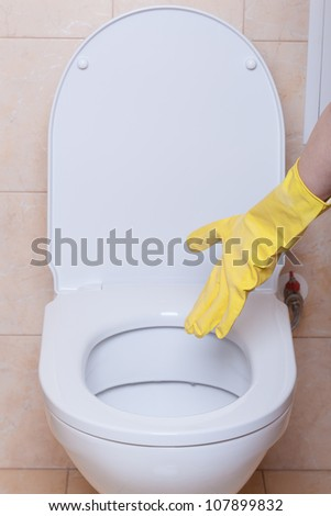 WC hygiene concept, hand in yellow glove making signs
