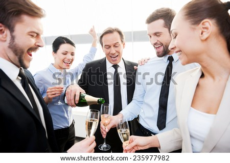 We absolutely deserve this! Group of happy business people holding flutes while mature man pouring champagne  - stock photo