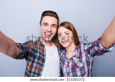 We are beautiful! Happy young loving couple making selfie while standing against grey background - stock photo