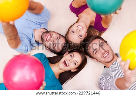 We are happy together. Cheerful friends lying down and outstretching their bowling balls  - stock photo
