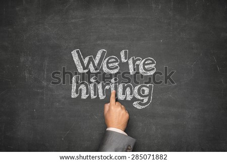 We are hiring concept on black blackboard with businessman hand - stock photo