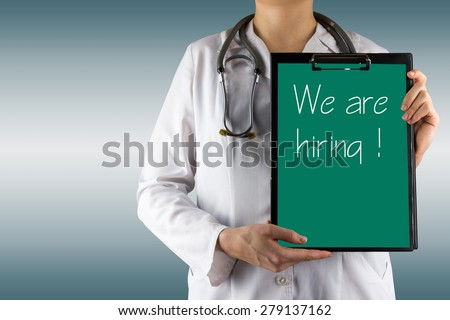 We are hiring ! - Female doctor's hand holding medical clipboard and stethoscope on blue blurred background. Concept of Healthcare And Medicine. Copy space - stock photo