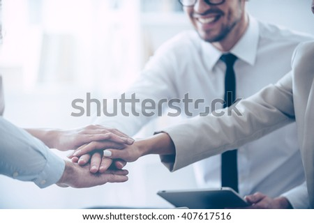 We are real team! Close-up part of top view of group of four young people holding hands and showing their unity with smile while sitting at office  - stock photo