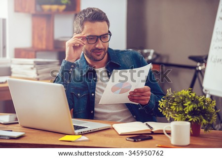 We are showing good results! Handsome young man holding paper with colorful diagram and looking at it while sitting at his working place in office - stock photo