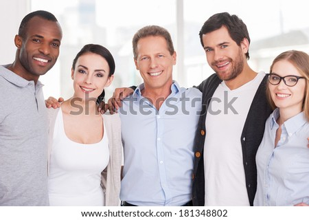 We are strong creative team! Group of cheerful business people in casual wear standing close to each other and looking at camera - stock photo