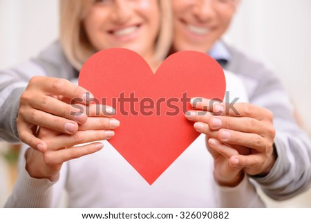 We are the one. Selective focus of heart in hands of adult loving couple holding it and expressing love - stock photo