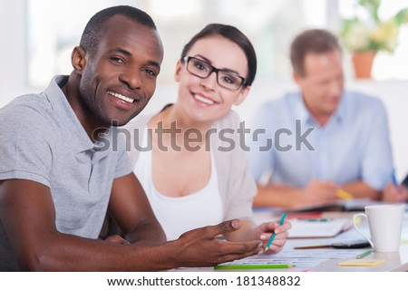 We are young and creative! Two business people sitting together at the table and smiling while other people working on background - stock photo