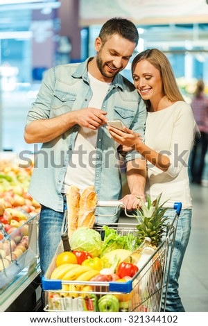 We bought all we need. Happy young couple looking at mobile phone together while standing near shopping cart in food store - stock photo