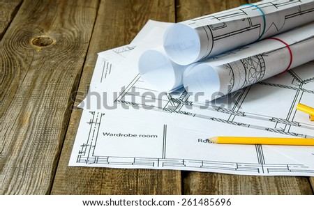 We build a building. House construction. Many drawings for building and pencils on old wooden background.
