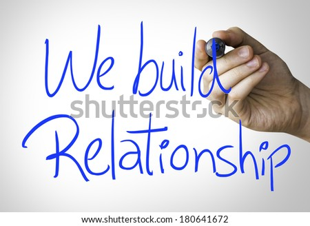 We build relationship hand writing on blue marker on transparent wipe board - stock photo