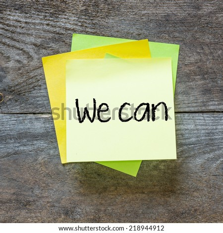 We can - motivational slogan on a stack of sticky notes posted on cork bulletin board - stock photo