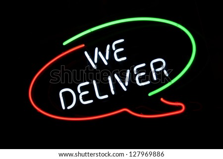We Deliver sign in Italian colors on pizzeria's window - stock photo
