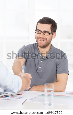 We have a deal. Two business people in casual wear handshaking while one of them smiling - stock photo