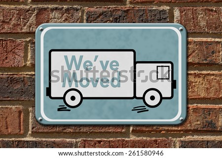 We have Moved Sign,  A blue sign with the word We've Moved with a truck on a brick wall - stock photo