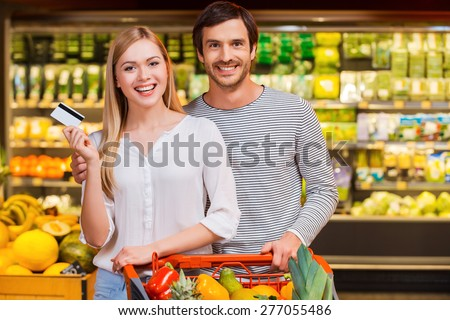 We like shopping together. Cheerful young couple smiling at camera and showing a credit card while standing in a food store - stock photo