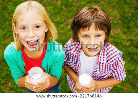 We love milk. Top view of two cute little children with milk moustaches holding glasses with milk and smiling while standing on green grass together  - stock photo
