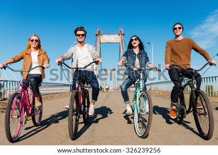 We love riding together. Full length of four young people riding their bicycles and smiling - stock photo