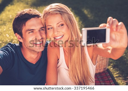 We love selfie! Happy young loving couple making selfie and smiling while sitting together on the grass in park - stock photo