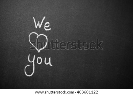 We Love You. Handwritten message on a chalkboard with an illustrated heart used as a symbol of love in this Valentines message.