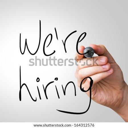 We're Hiring hand writing with a black mark on a transparent board - stock photo
